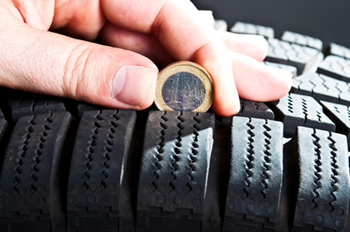 Mindestprofil von Autoreifen mit einer Euro-Münze prüfen.